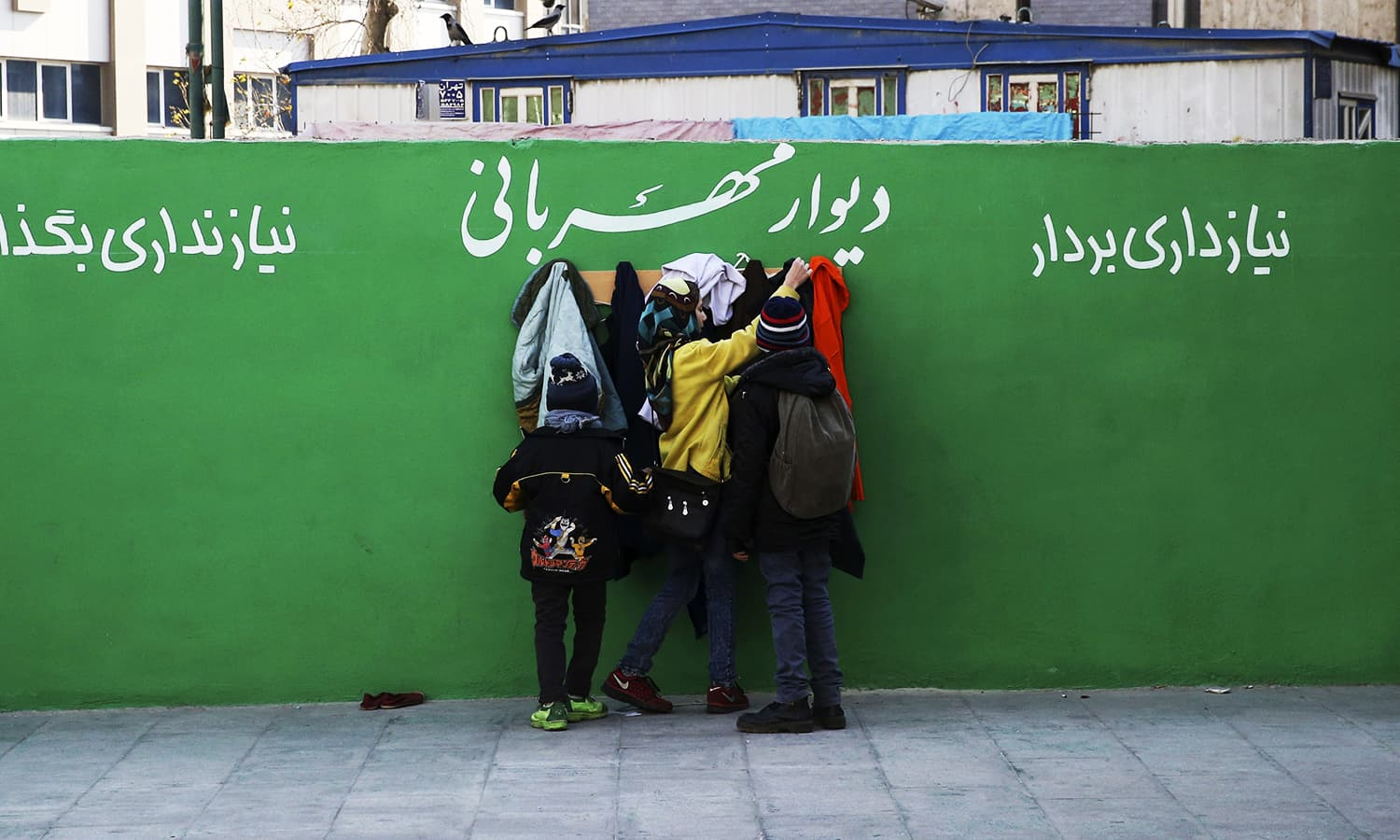 """In this Thursday, Jan. 7, 2016 photo, youths check clothes hung on hooks at an outdoor charity wall marked, """"Wall of Kindness,"""" next to a subway station entrance in central Tehran, Iran. ─ AP"""