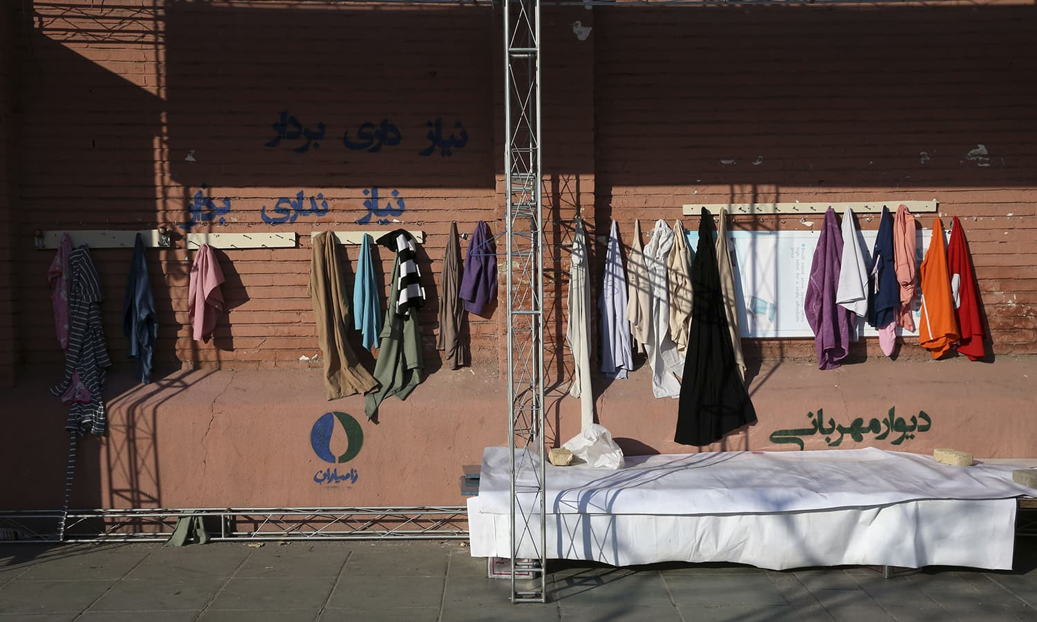 """In this Thursday, Jan. 7, 2016 photo, clothes hang on an outdoor charity wall with writing in Farsi at bottom right that reads, """"Wall of Kindness,"""" in downtown Tehran, Iran. ─ AP"""