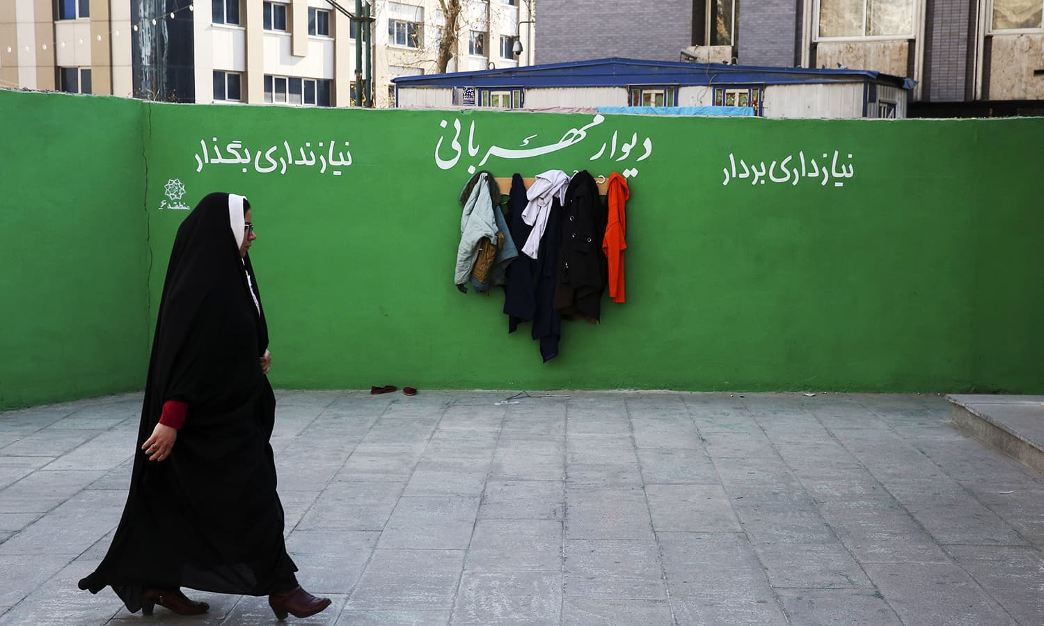 """In this Thursday, Jan. 7, 2016 photo, an Iranian woman walks past clothes hung on hooks at an outdoor charity wall marked, """"Wall of Kindness,"""" next to a subway station entrance in central Tehran, Iran. ─ AP"""