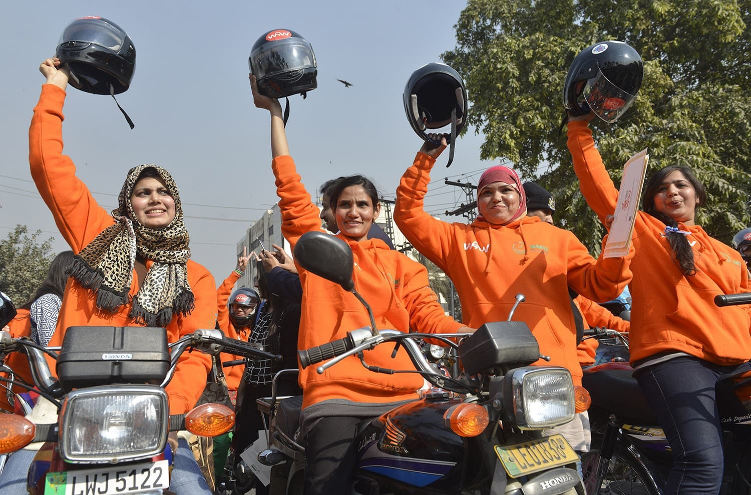 Women participants of Women on Wheels (WOW) raise their helmets at the start of a rally launching the Women on Wheels campaign in Lahore.─AFP