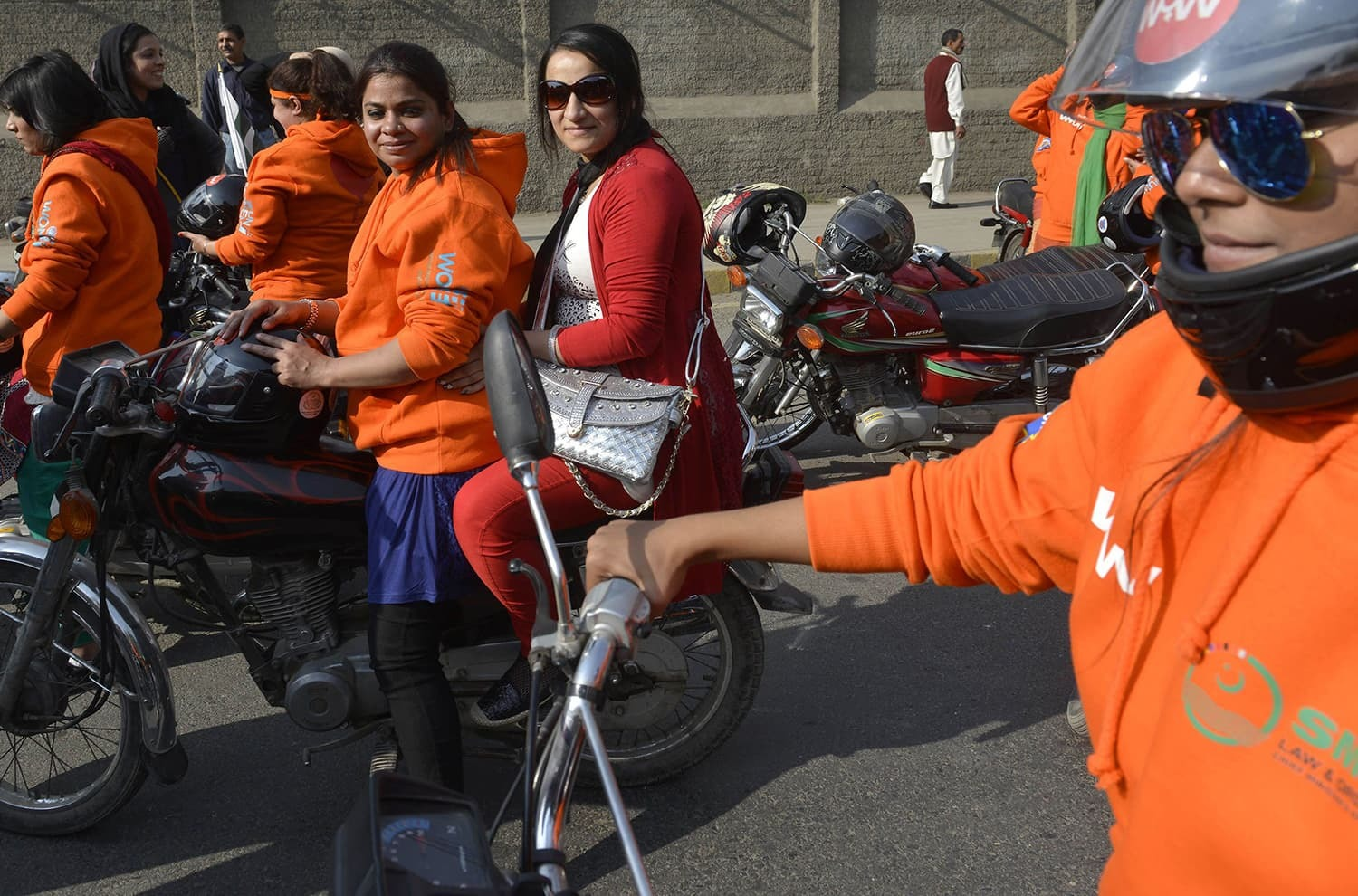 Women participants of Women on Wheels (WOW) wait on their motor-bikes prior to the start of a rally launching the Women on Wheels campaign in Lahore on January 10, 2016. ─ AFP