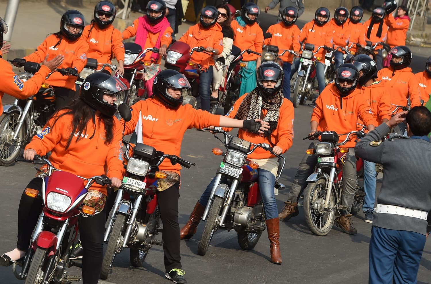 Women participants of Women on Wheels (WOW) prepare to ride their motorbikes during a rally launching the Women on Wheels campaign in Lahore on January 10, 2016.─ AFP.
