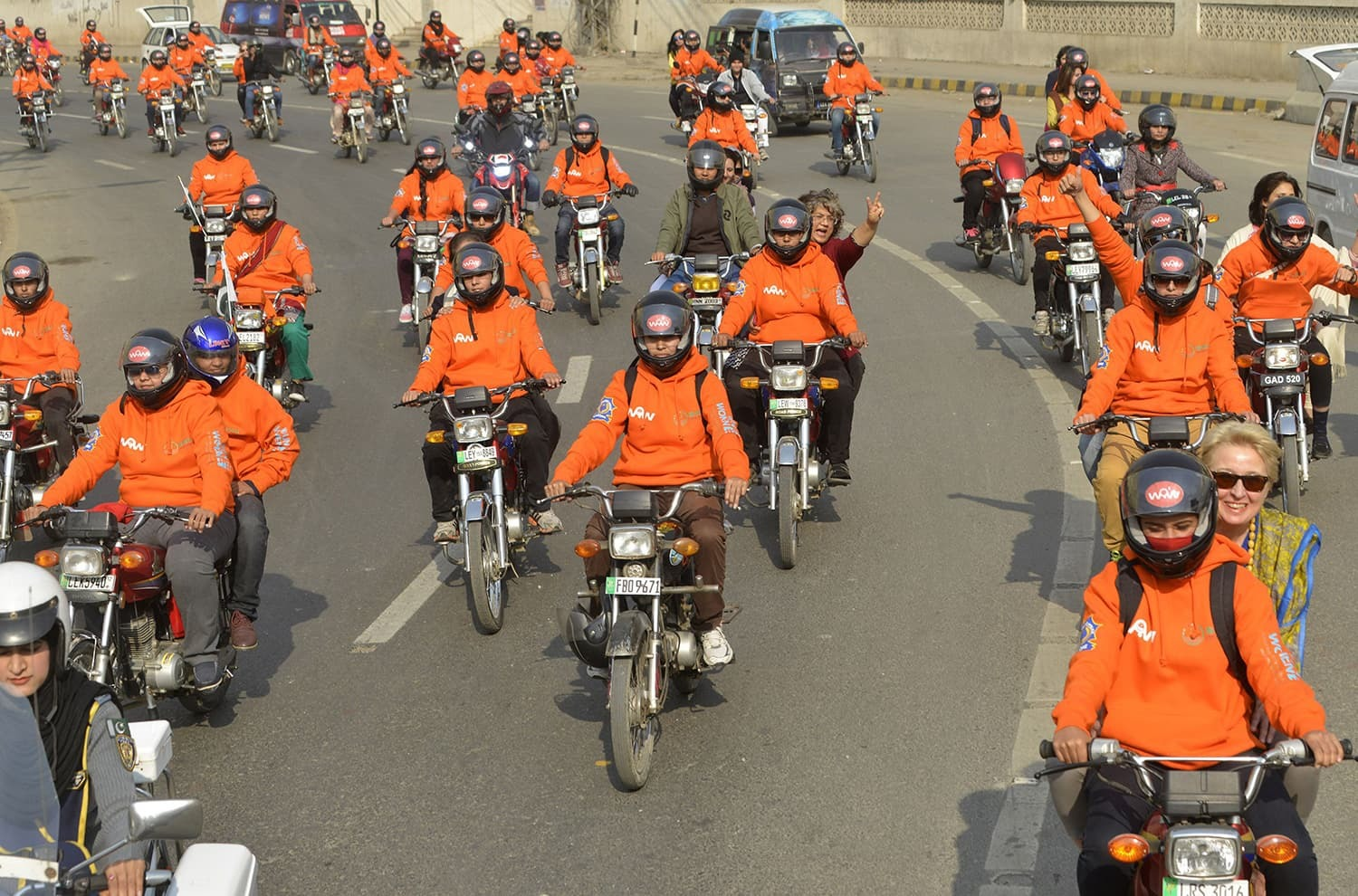 Women participants of Women on Wheels (WOW) ride their motor-bikes during a rally launching the Women on Wheels campaign in Lahore.─AFP
