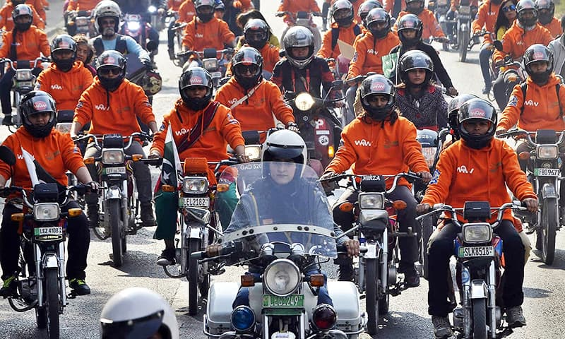 Participants of Women on Wheels (WOW) ride their motor-bikes during a rally in Lahore. ─AFP
