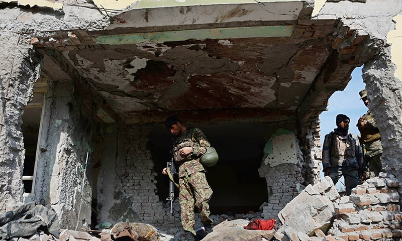 Afghan security personnel inspect a building used by insurgents to launch an attack on the Pakistan consulate in Jalalabad. -AFP