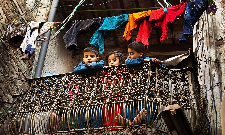 ایک بالکونی سے بچے اس شہر کو دیکھ رہے ہیں جو ان کی آنکھوں کے سامنے تیزی سے بدلتا جا رہا ہے۔ — فوٹو کاپی رائٹ خلیل شاہ۔ اس تصویر کے جملہ حقوق بحقِ فوٹوگرافر محفوظ ہیں۔