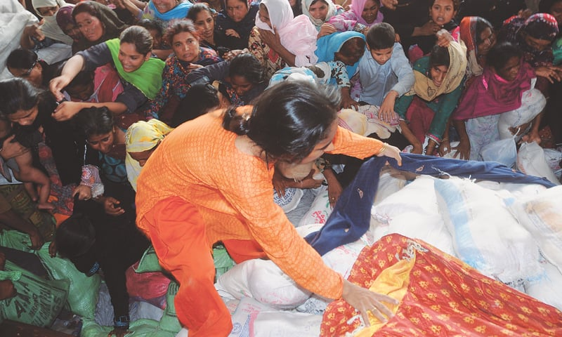Women and girls scramble to secure a bag of wheat at a rations distribution in Karachi