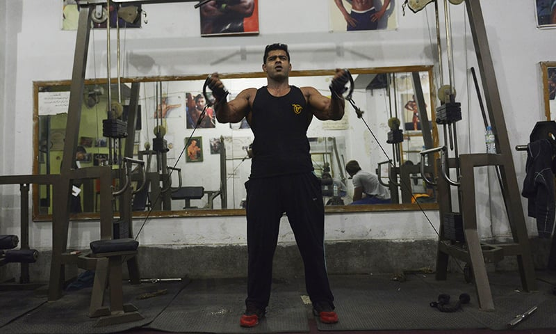 Salman Ahmed excercises at his gym in Lahore. — AFP