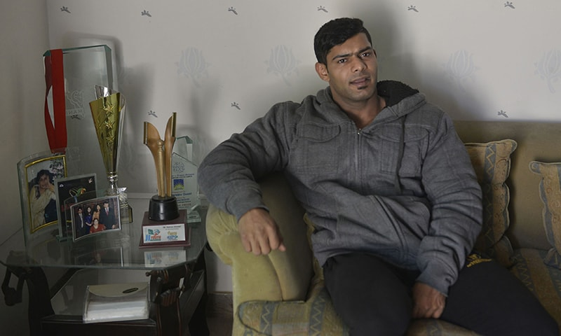 Salman Ahmed sits next to a selection of his awards as he speaks his home in Lahore.