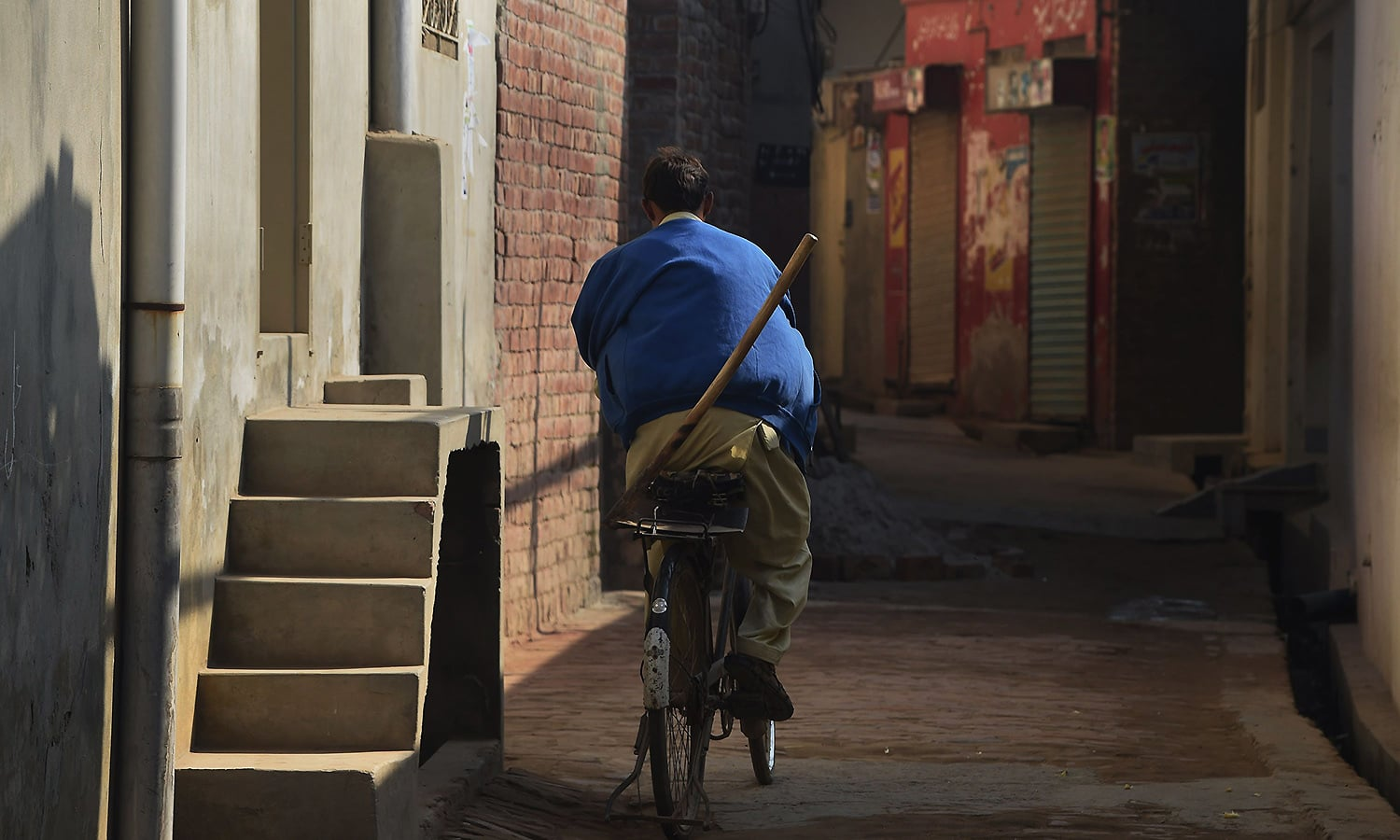 A Pakistani victim of child abuse rides his bicycle along a street in Hussain Khan Wala village on November 20, 2015. ─ AFP
