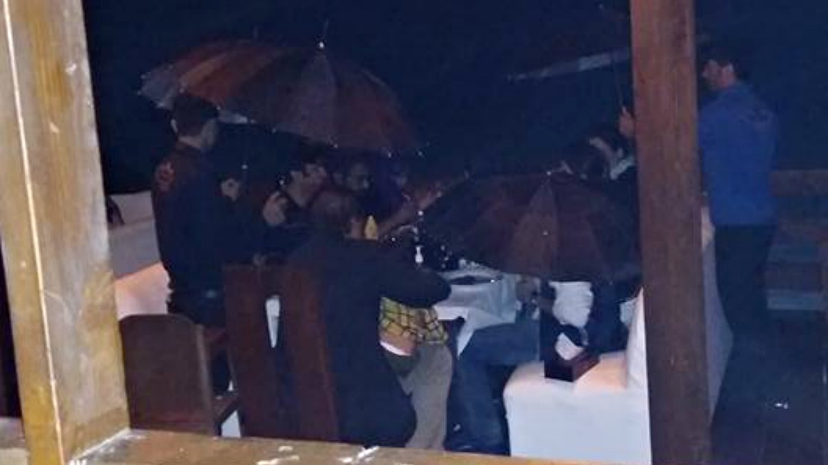 Waiters flock around a family holding up umbrellas to shield them from the rainfall