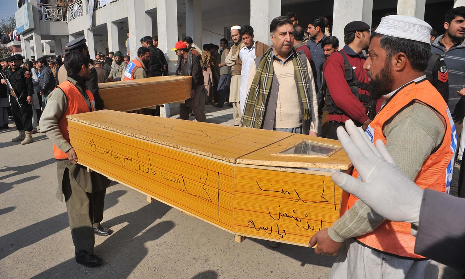 Rescue workers carry coffins at a local hospital. Emergency was declared across hospitals in the province, and PTI's Shaukat Yousafzai told media some of the injured were taken to Peshawar.— AFP
