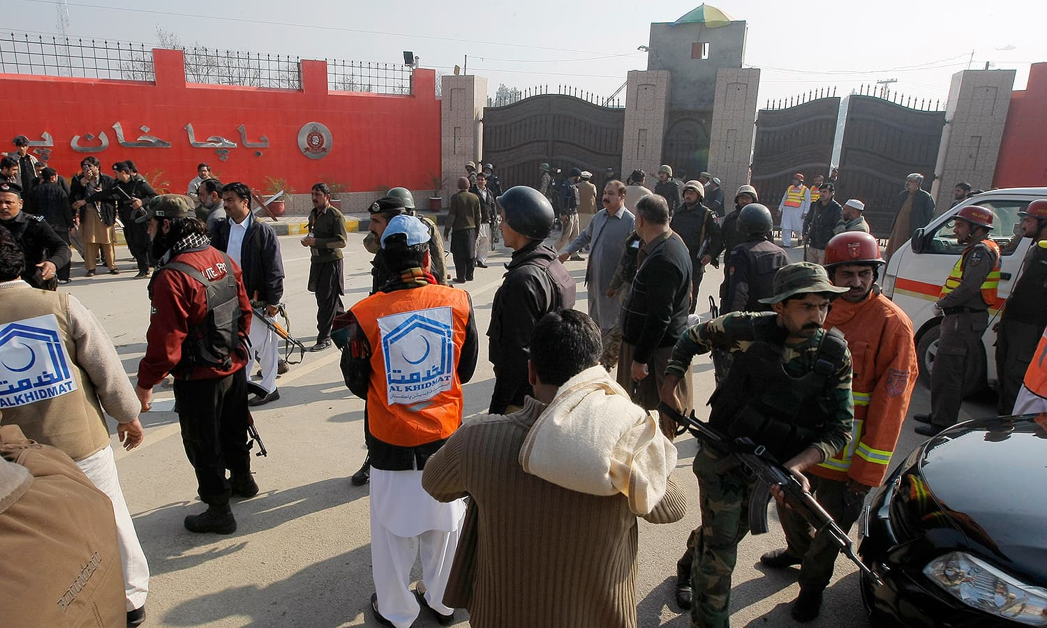 Troops and rescue workers gather at the main gate of the university. — AP