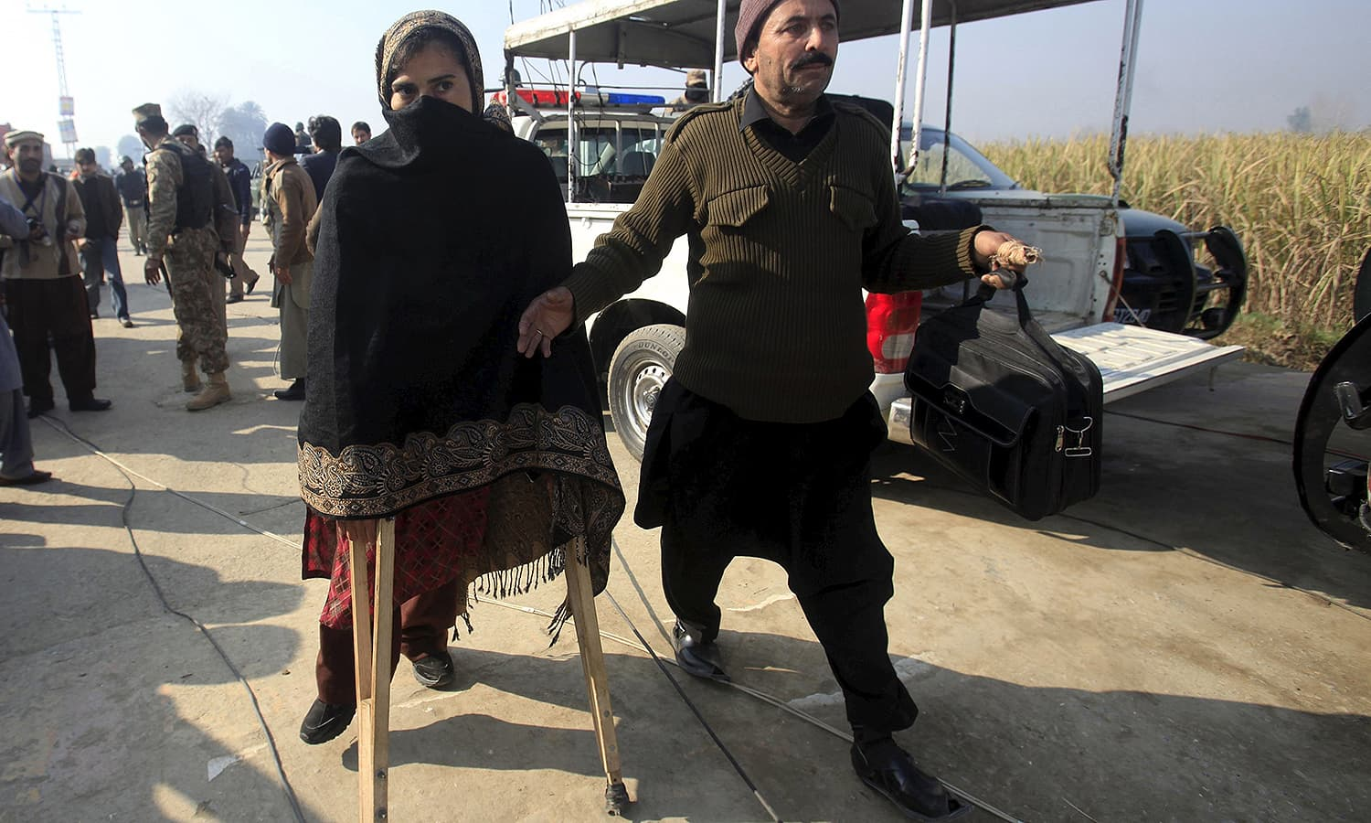 A teacher (L) walks with a pair of crutches following her rescue. Vice Chancellor Fazal Rahim told reporters that the university teaches over 3,000 students and was hosting an additional 600 visitors on Wednesday for the recital. Students spoke of one teacher, named by the media as Syed Hamid Hussain, fighting back against the intruders, shooting his weapon in a bid to protect his students. — Reuters