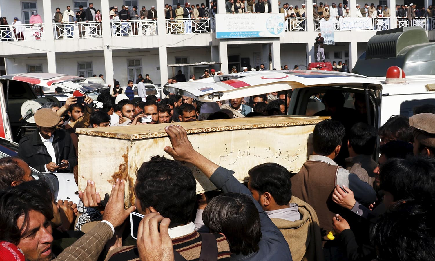 Relatives and friends surround the coffin of a student, who was killed in a militant attack at Bacha Khan University, outside a hospital in Charsadda. -Reuters