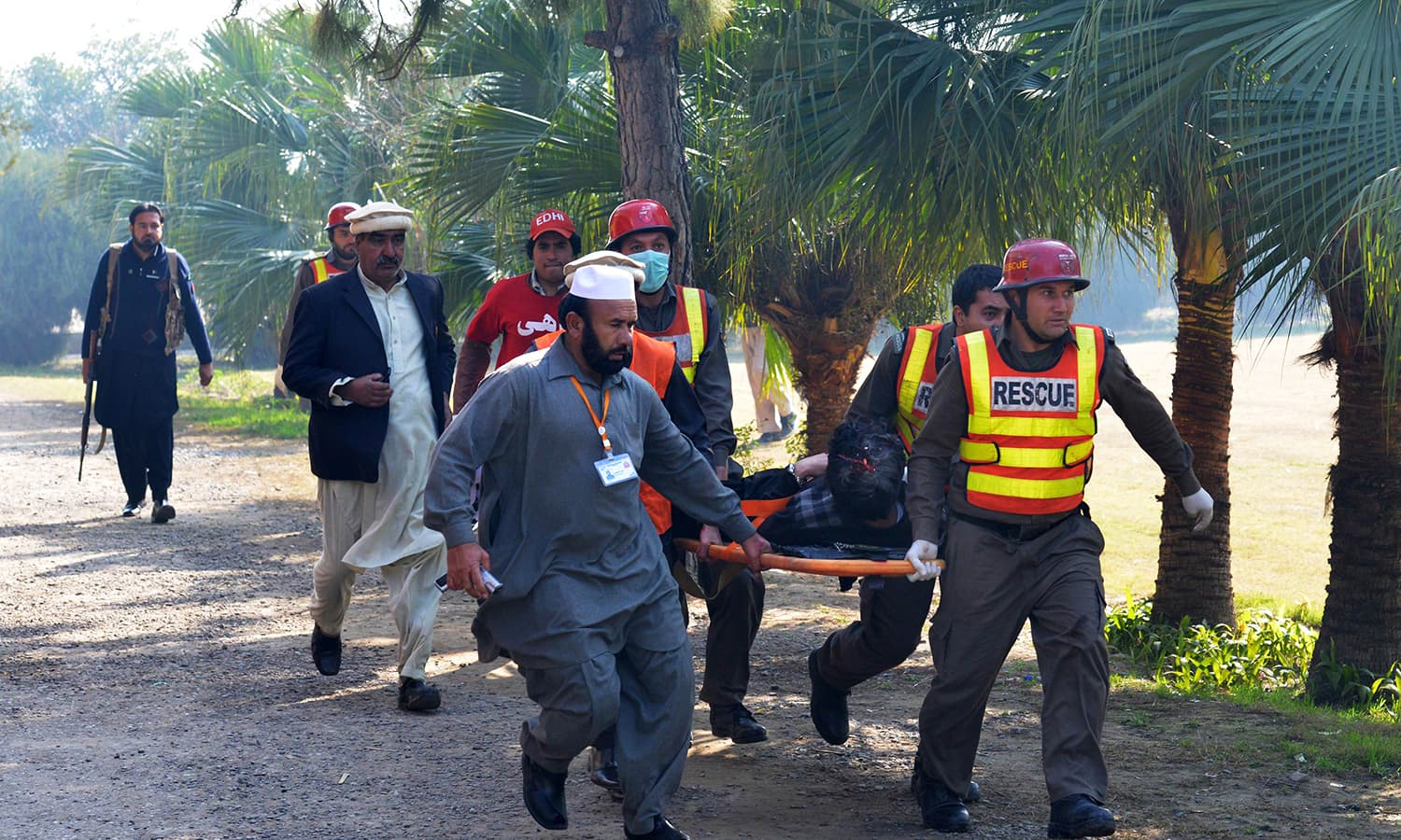 Pakistani rescue personnel carry a victim at Bacha Khan university following an attack by militants in Charsadda. -AFP