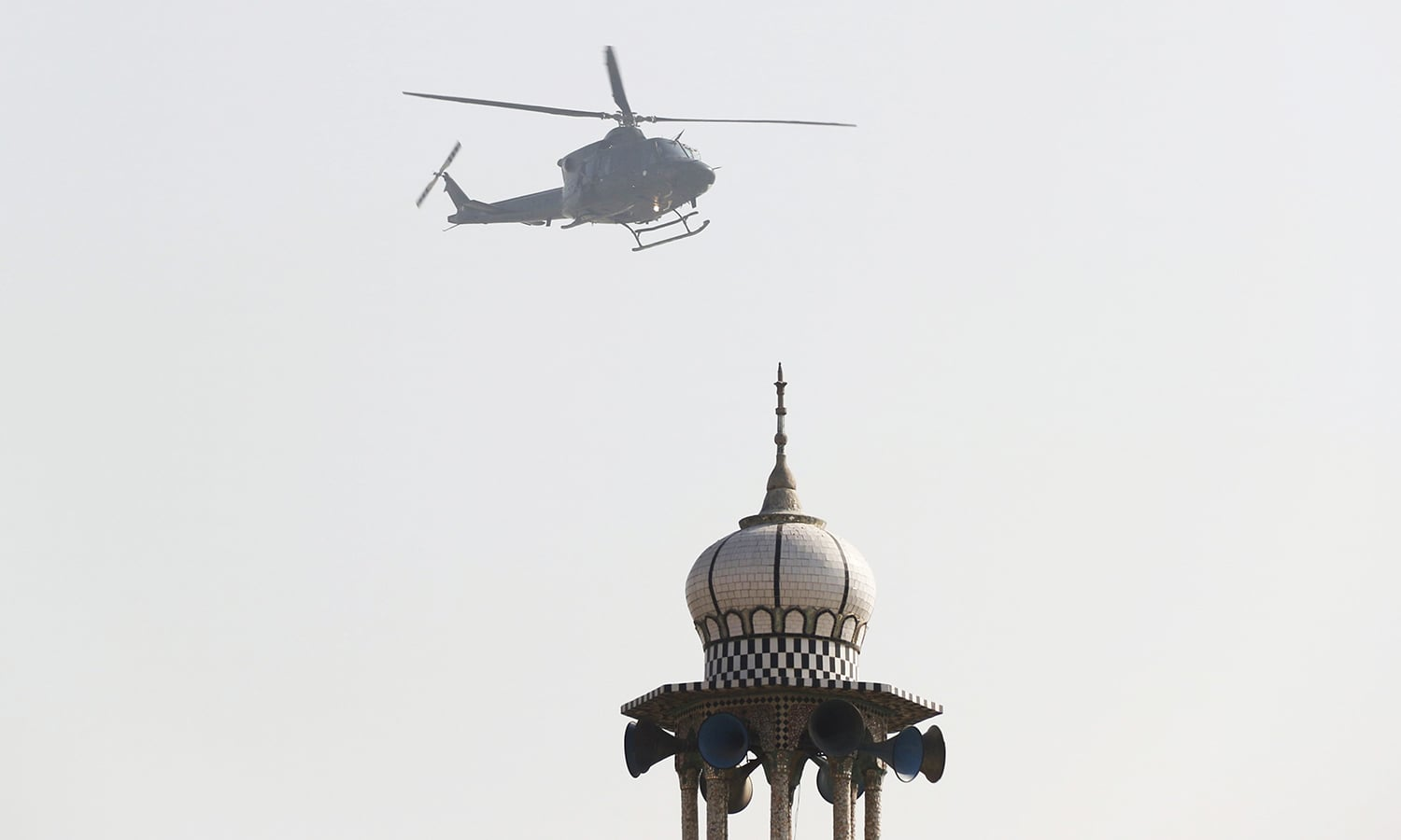 A Pakistan Army helicopter flies past a mosque during an operation after a militant attack at Bacha Khan University. -Reuters