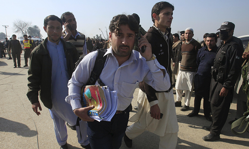 A student holding his books talks on a mobile phone, after he was rescued in a militant attack at Bacha Khan University in Charsadda.─ Reuters