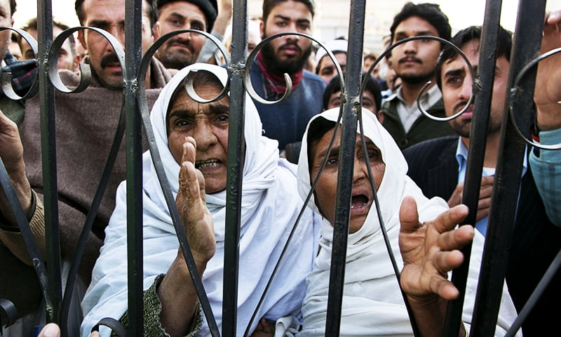Family members wait outside a hospital where injured people were taken after the Bacha Khan University attack. ─ AP