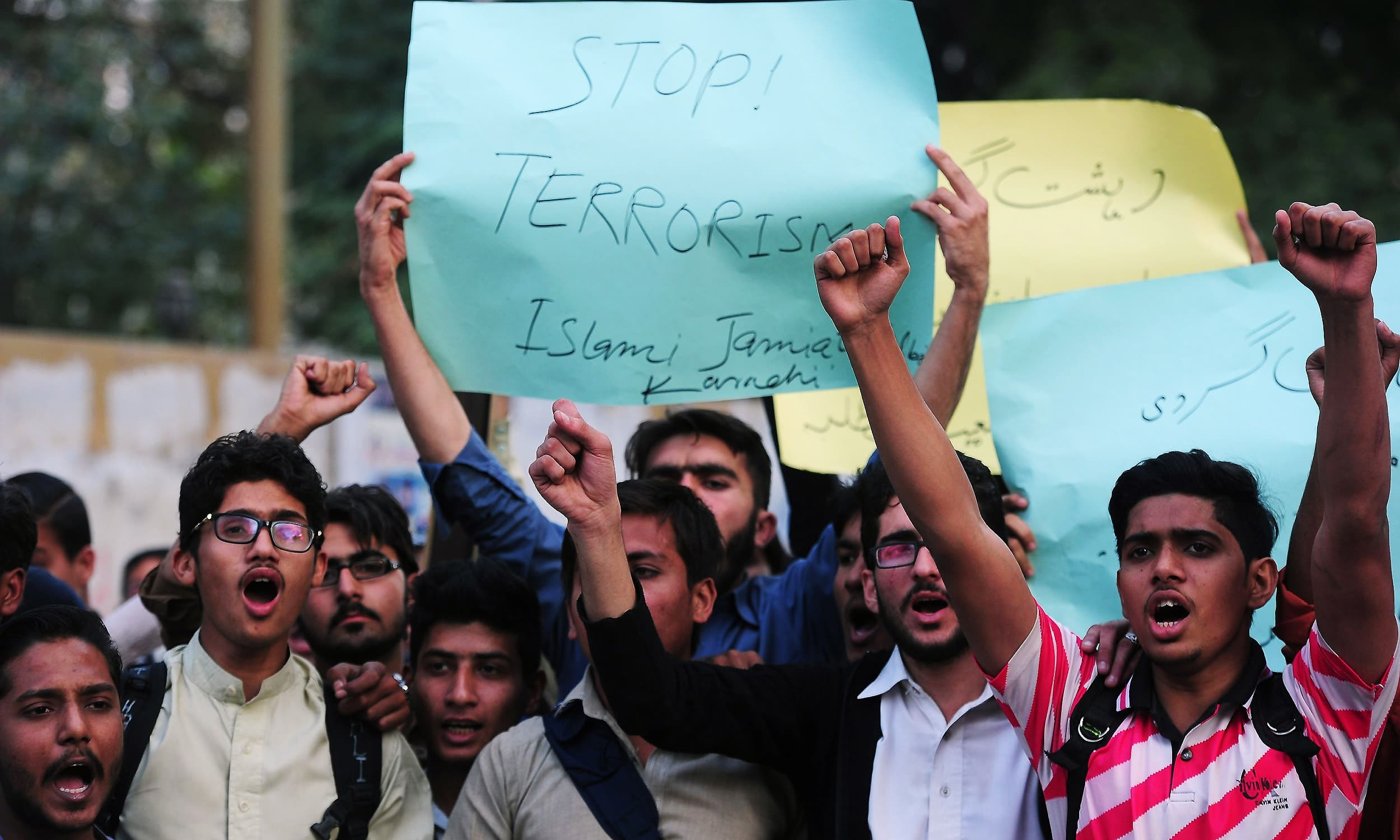 Members of a student's wing of a political party in Karachi shout slogans protesting the militant attack on Bacha Khan University. ─ AFP