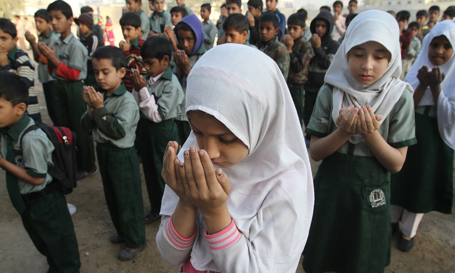Students pray for victims of Bacha Khan University, at a school in Karachi, Pakistan, Thursday, Jan. 21, 2016. — AP