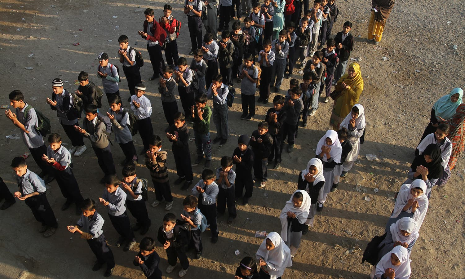 Students pray for victims of Bacha Khan University, at a local school in Karachi, Pakistan, Thursday, Jan. 21, 2016. — AP