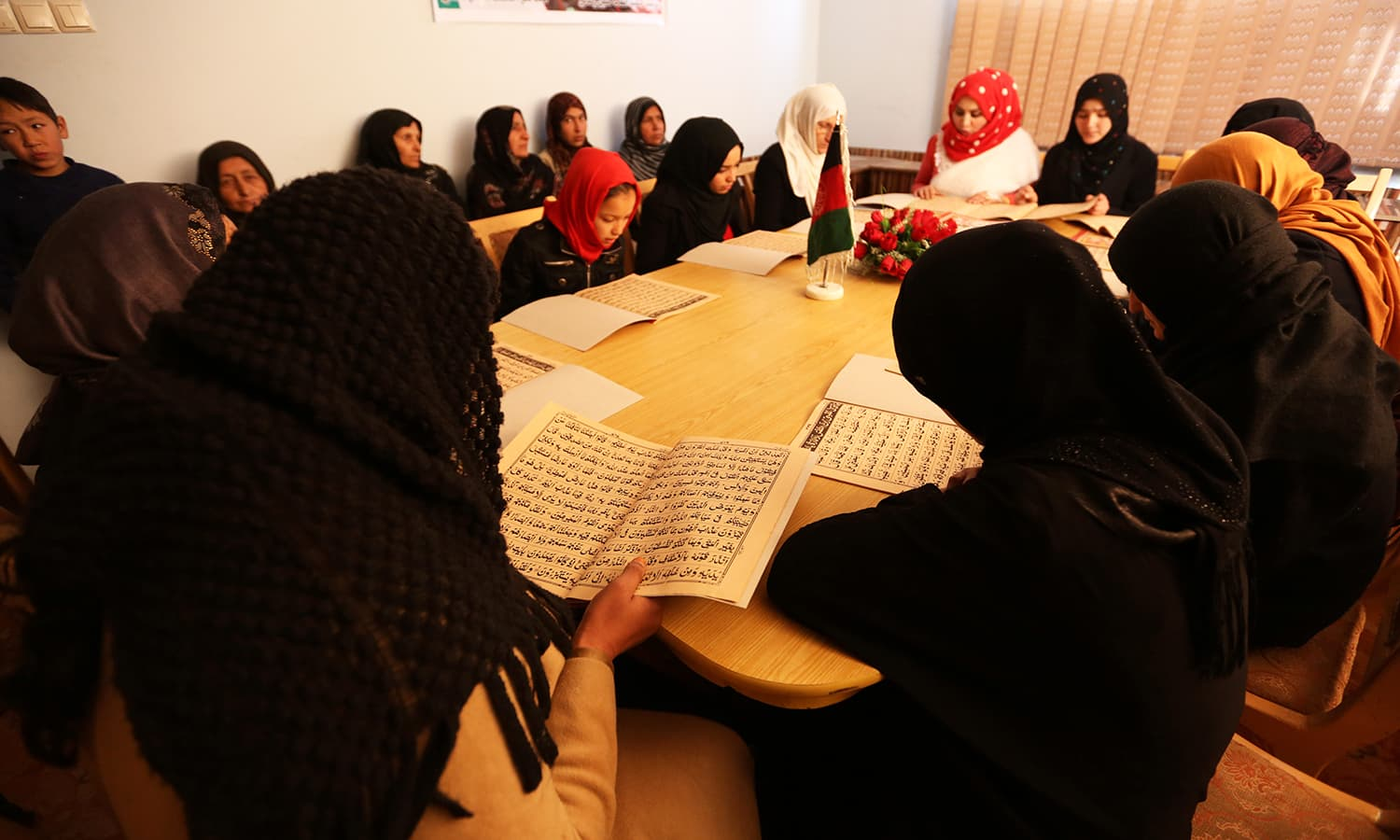 Afghan women read the Holy Quran at the office of Afghanistan General association of public servants in Kabul. - AP