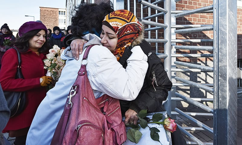 A woman hugs a migrant after giving a flower to her outside of a refugee home in Cologne, Germany, Friday, Jan 22, 2016. Following the New Year's Eve attacks in Cologne, refugees handed out flowers to women in different cities as sign of good will. Several dozen women visited Cologne's biggest refugee center to return the favour.—AP
