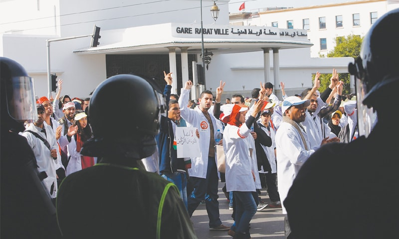 Rabat (Morocco): Riot police officers form a line as trainee teachers march in the capital, denouncing government measures that would trim the education branch of the public sector through cuts in grants and jobs here on Sunday.—AP