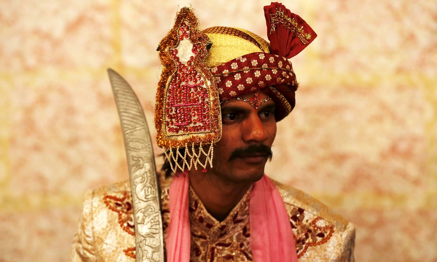 A groom in traditional dress waits for his wedding to start. ─ Reuters