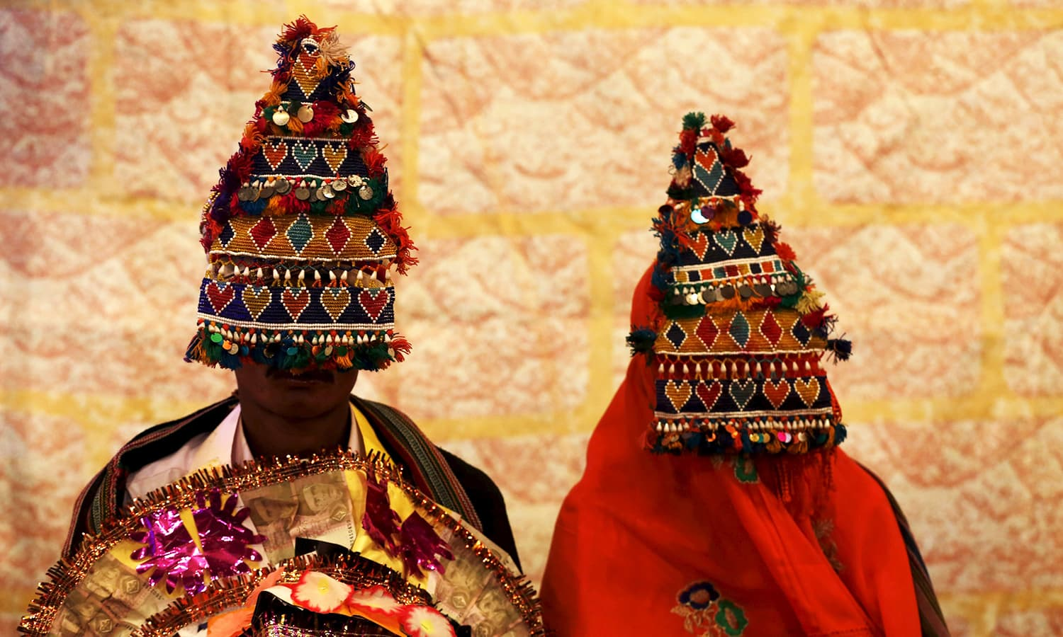 A bride and groom wearing traditional handmade garlands wait for their wedding to start during a mass marriage ceremony in Karachi organised by the Pakistan Hindu Council. ─ Reuters