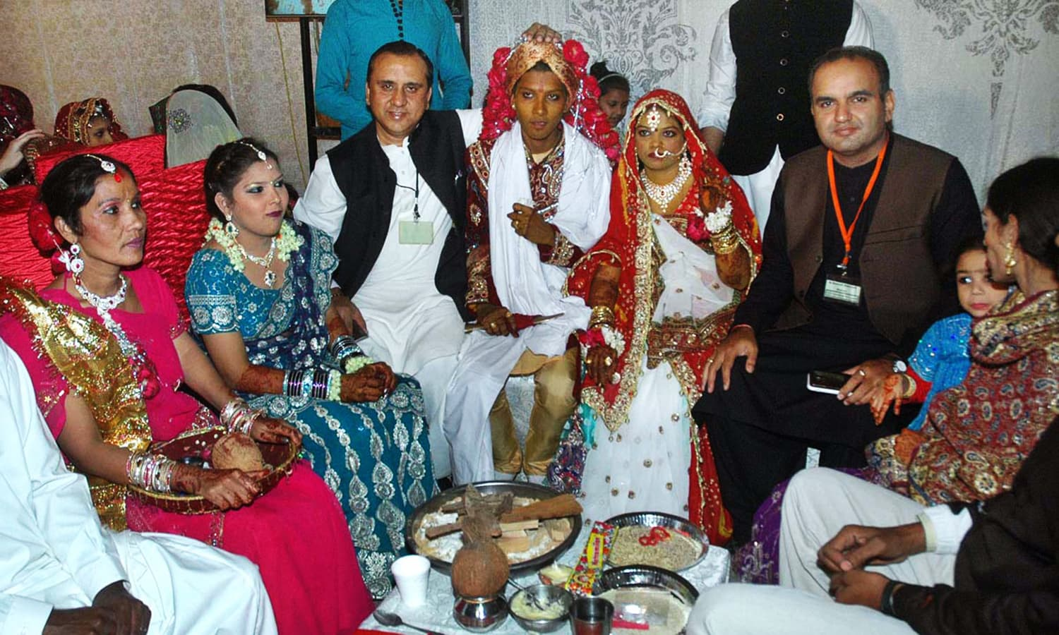 Patron of the Pakistan Hindu Council, Dr.Ramesh Vankwani, in a group photo during the mass marriage ceremony of 60 couples organised by the PHC. ─ APP