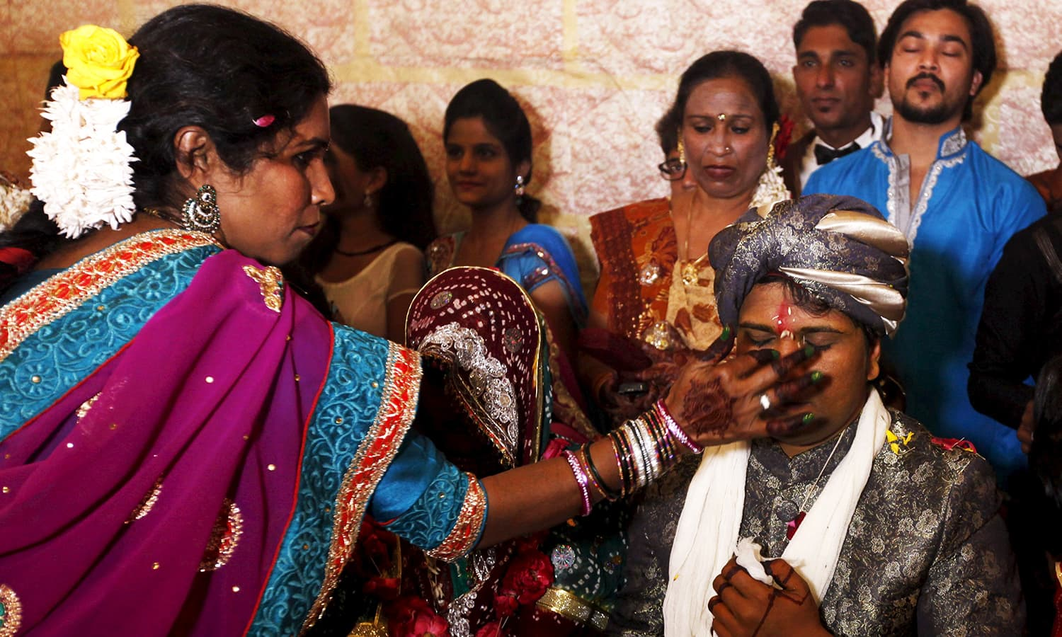 A groom receives a dot on his forehead with Sindoor during a mass marriage ceremony. ─ Reuters