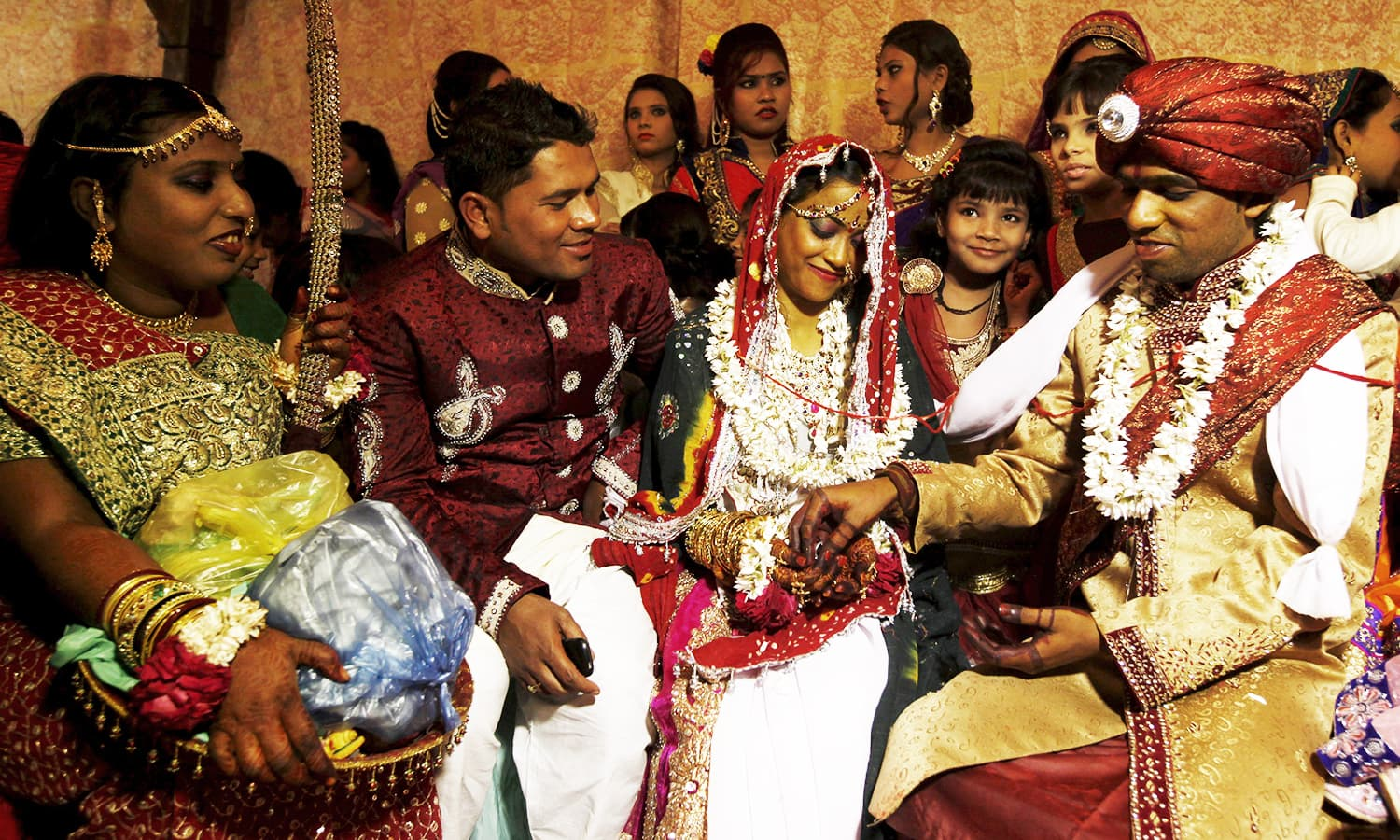 A bride and groom couple go through a ritual during a marriage ceremony. ─ Reuters