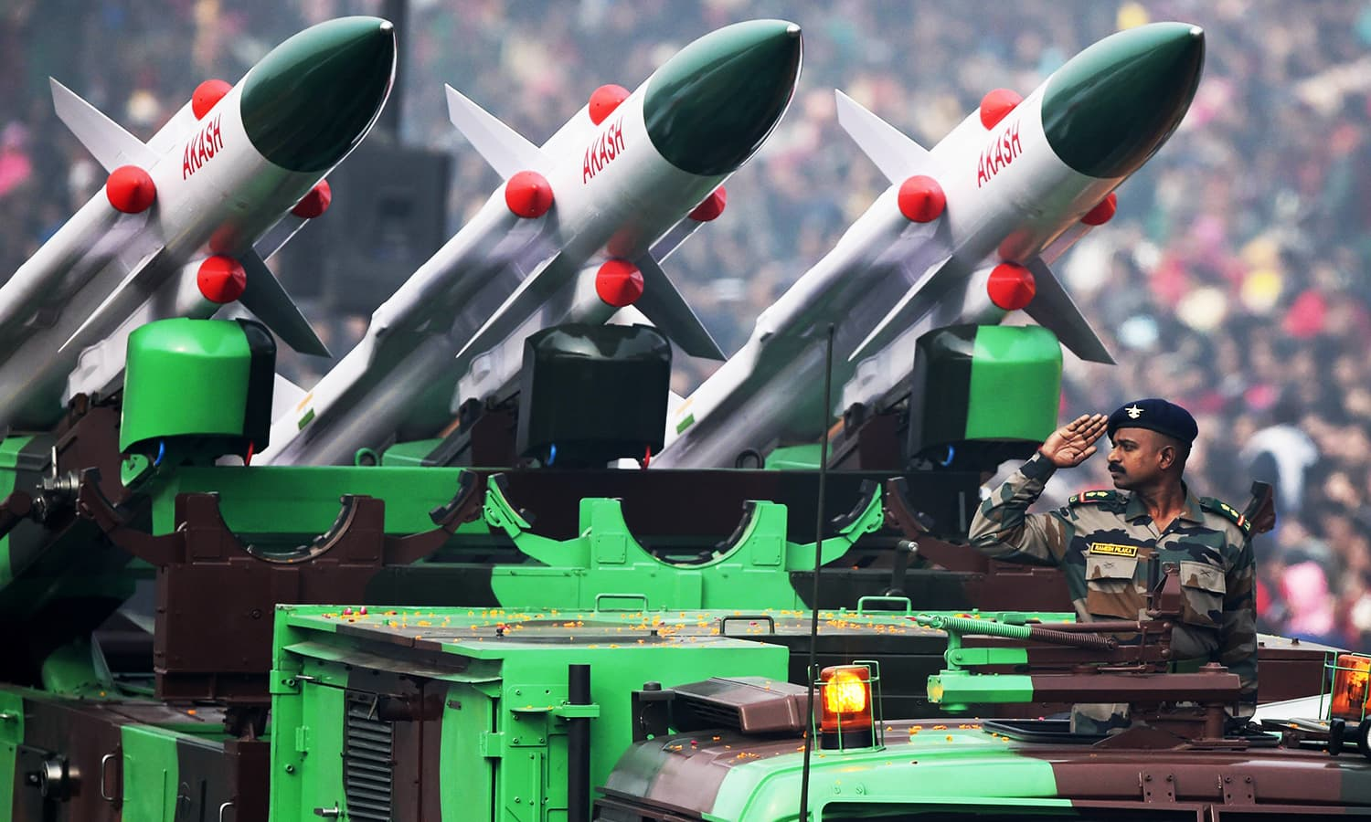 An Indian soldier salutes as he rides an Akash weapon system of air defence during India's Republic Day parade. ─ AFP