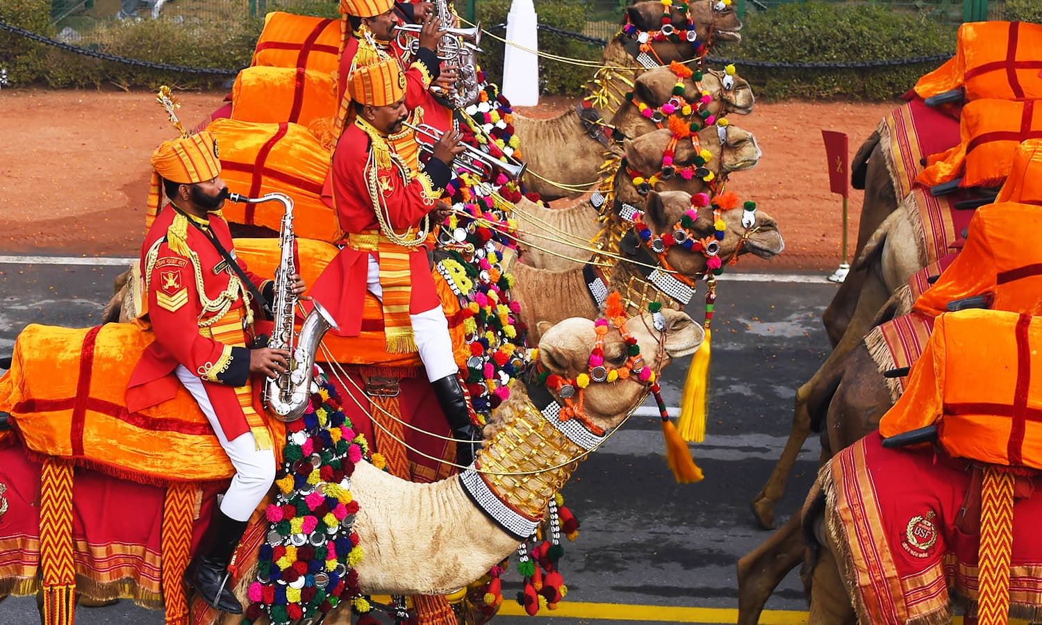 A member of the band of the Border Security Force contingent plays a saxophone on his camel during the parade. ─ AFP