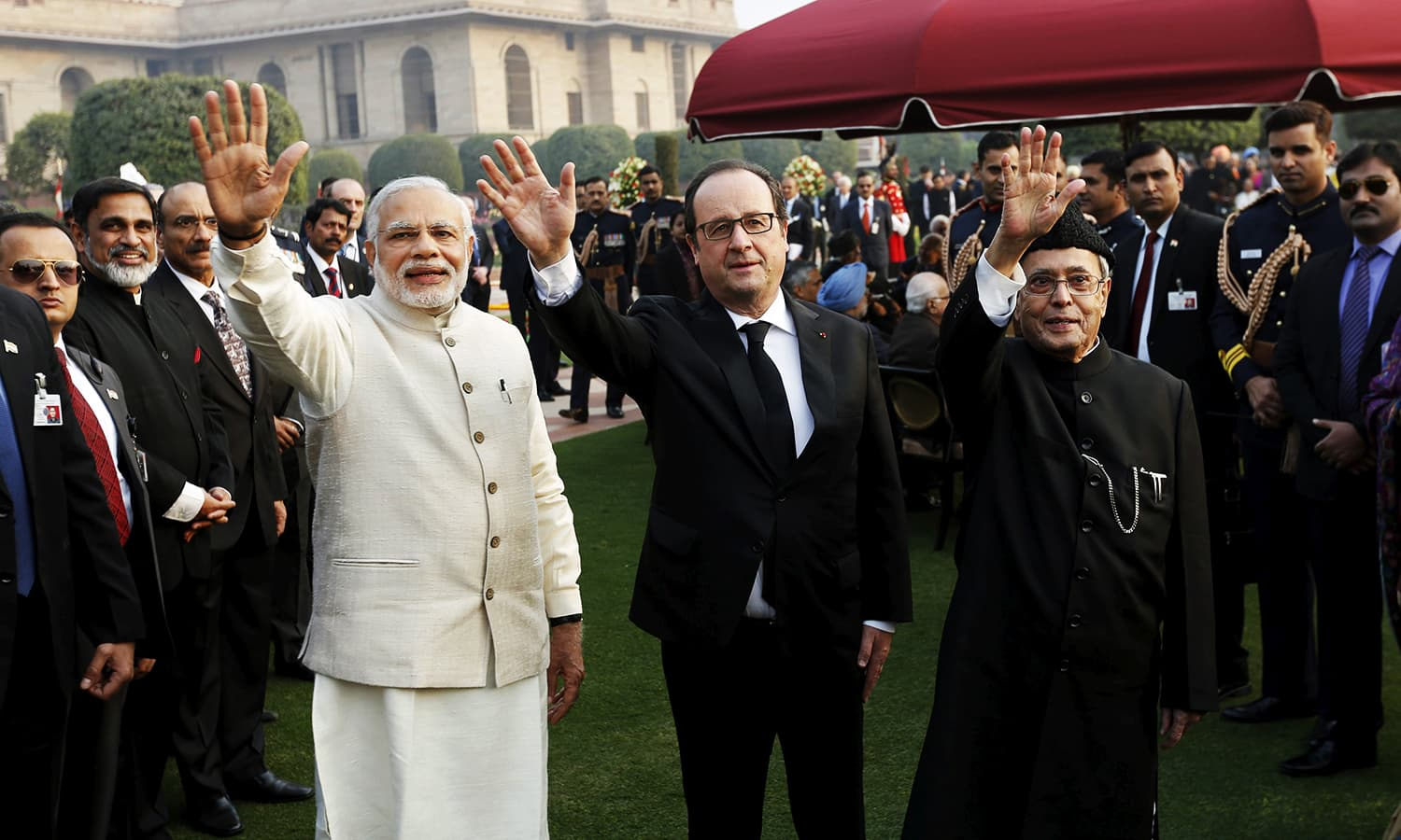 (L-R) India's Prime Minister Narendra Modi, French President Francois Hollande and his Indian counterpart Pranab Mukherjee wave as they attend the 'At Home' reception at the Rashtrapati Bhavan presidential palace after the Republic Day parade. ─ Reuters