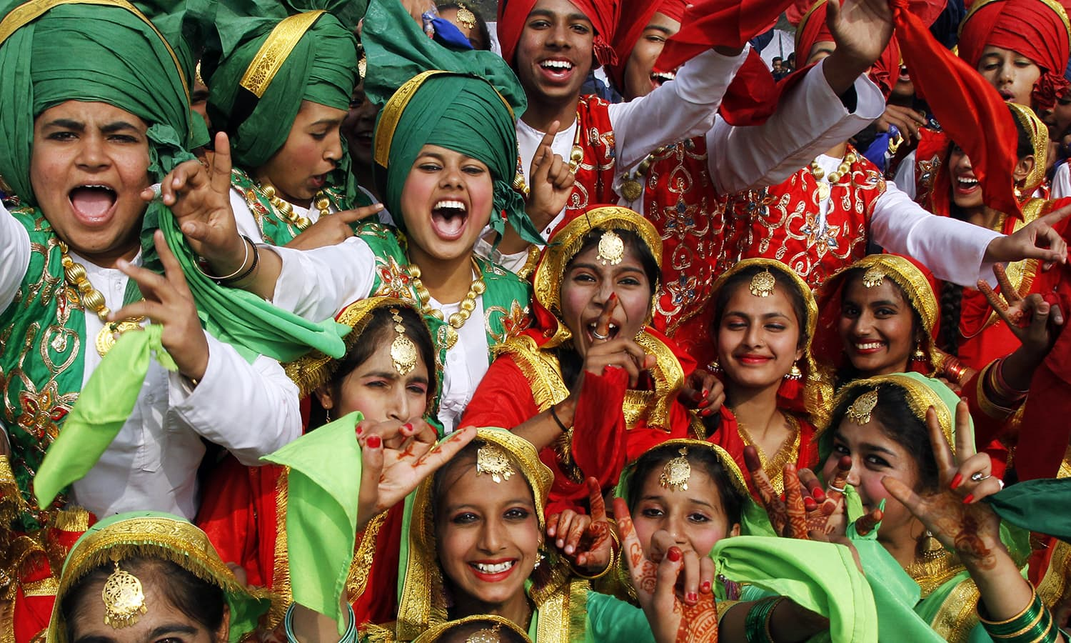 Schoolchildren wearing traditional attire cheer after performing at a cultural program during the Republic Day celebrations in Chandigarh, India. ─ Reuters