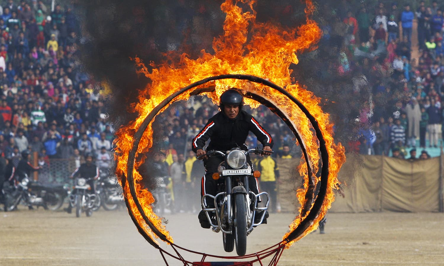 An India-Held Kashmir state policeman jumps through a fire wheel as he performs a motorcycle stunt. ─ AP