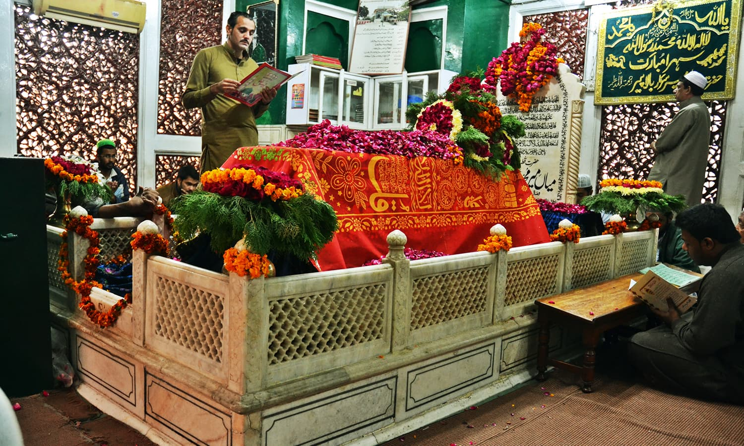 Mian Mir's grave covered with flowers while people recite the Quran. —Photo by Abdullah Khan