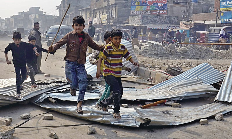 Children jump over iron sheets pulled down by protesters at Samanabad Morr. — White Star