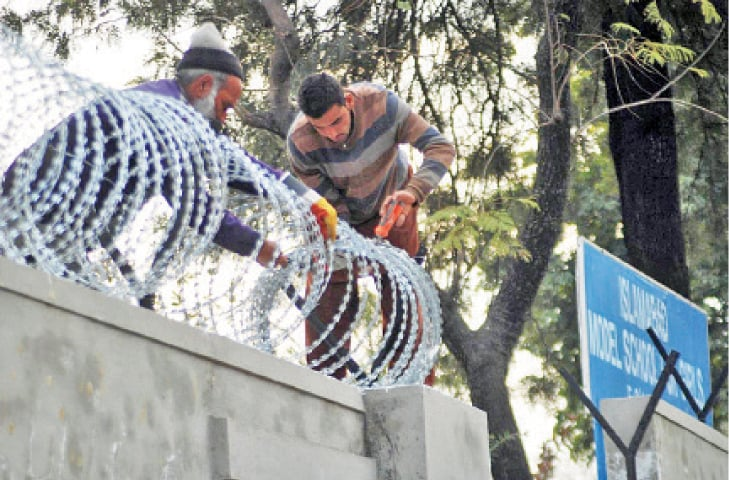 Workers install barbed wire on the wall of a school in Islamabad. —Online