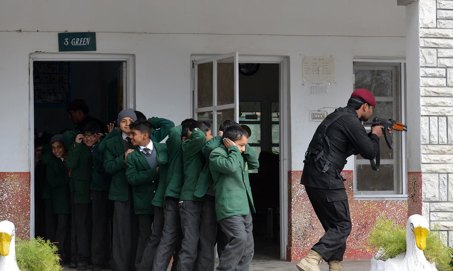 An Elite Police Force member takes part in a drill to fight against militants at a school in Peshawar. —AFP