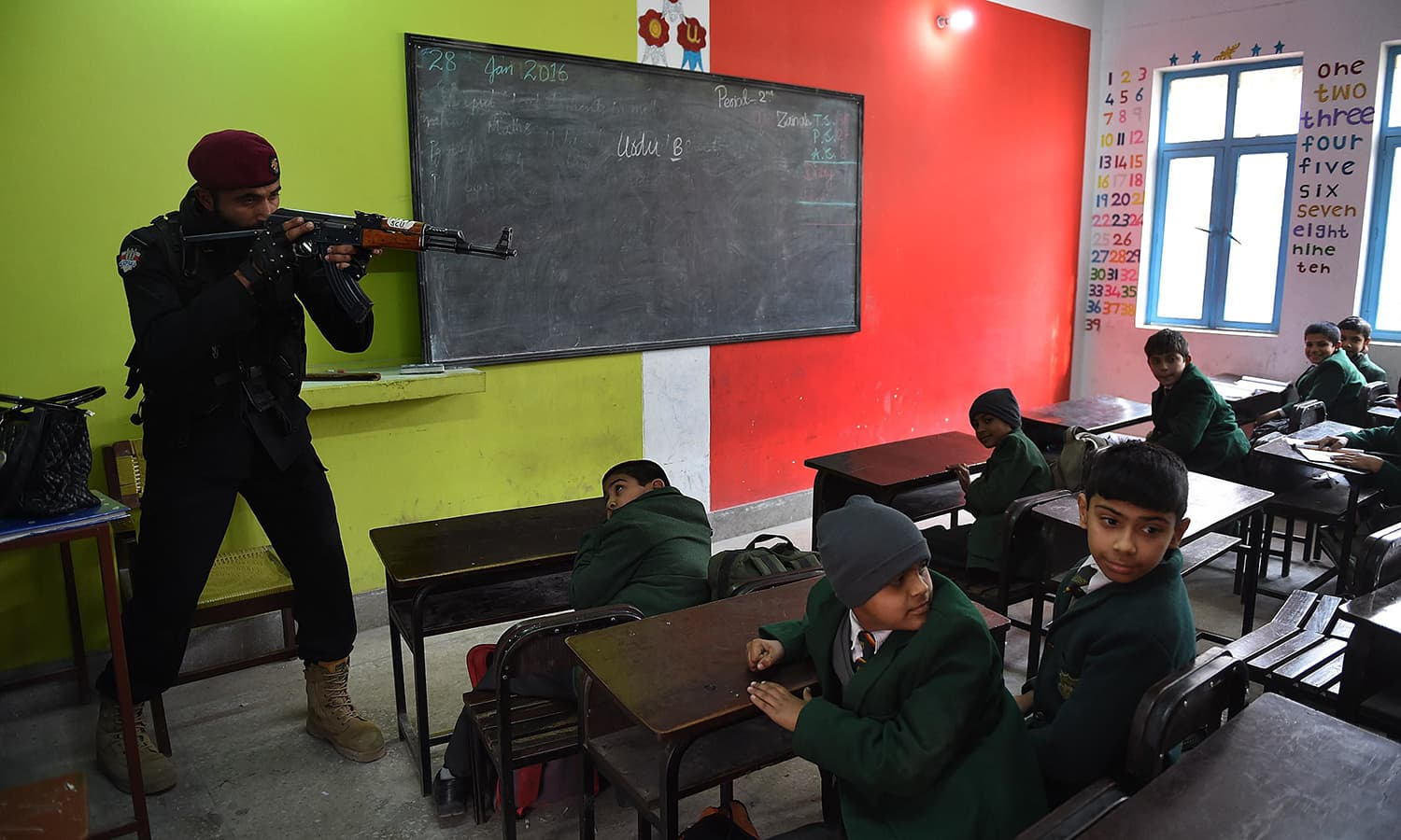 A police official takes part in a drill to fight against militants at a school in Peshawar. —AFP