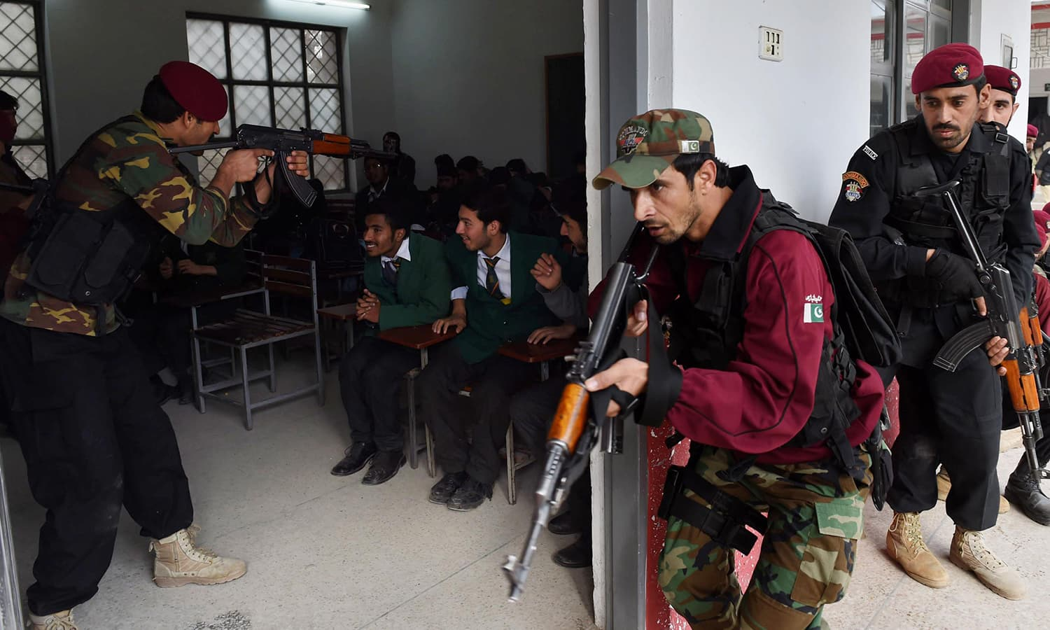 Security officials take part in a drill to fight against militants at a school in Peshawar. —AFP