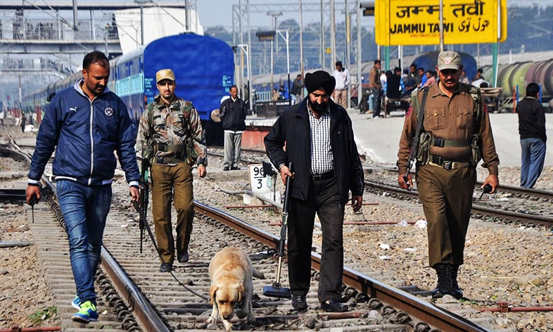 Indian police officials and dog squad members walk along railway tracks at a station in Jammu on January 3, 2016, after security was increased on railways in northern India following the Pathankot air base attack. ─ AFP/File