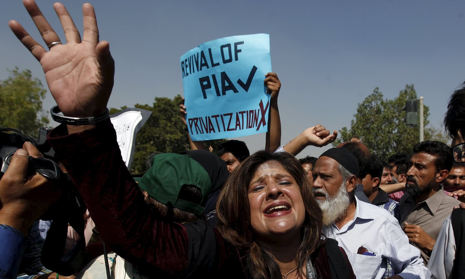 PIA Employees chant slogans as they march towards the Jinnah International Airport. ─ Reuters