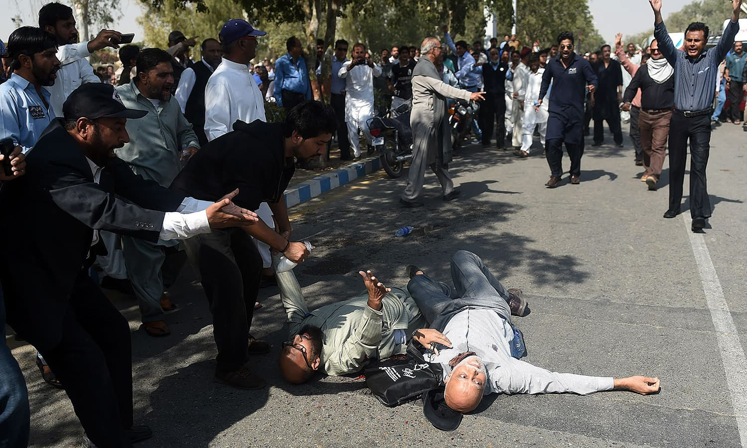 Protesting PIA employees gather around injured colleagues who were hit by bullets. ─AFP