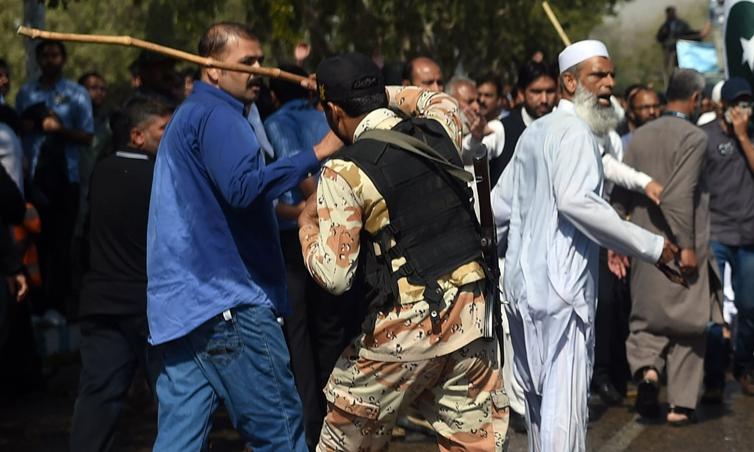 A paramilitary soldier charges with a wooden baton on PIA employees. ─AFP