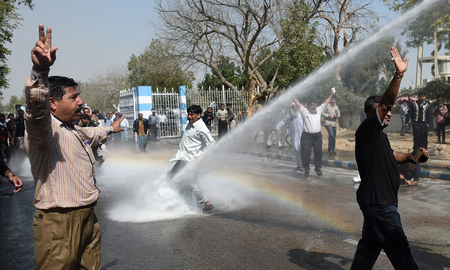 PIA employees shout slogans as police use a water cannon on them during a protest near the airport in Karachi.  ─AFP